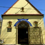 Napis nad wejściem do Kaplicy Na Brzegu: UZDRAWIA  KRÓLUJE  BŁOGOSŁAWI